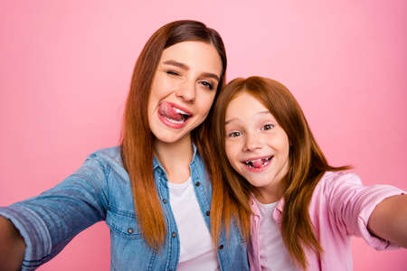 Close up of carefree people with ginger long haircut making photos grimacing wearing denim jeans shirt isolated over pink background Zdjęcie Seryjne