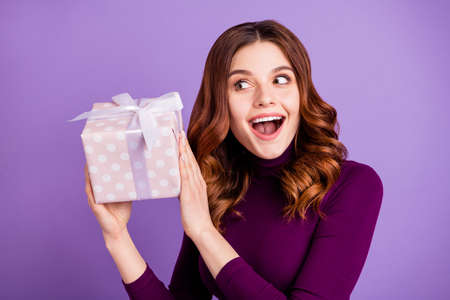 Close up photo of funny funky lady holding hand package giftbox shake isolated over purple violet background