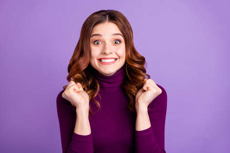 Close-up portrait of her she nice attractive lovely funny cheerful cheery optimistic wavy-haired girl holding fists good great news isolated over bright vivid shine purple violet lilac background Reklamní fotografie