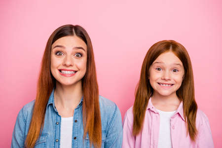 Close up photo of charming girls looking with beaming smile isolated over pink background