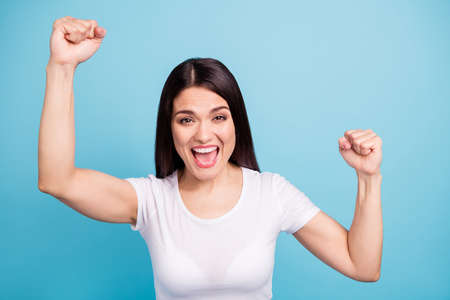 Photo of victorious ecstatic girlfriend overjoyed with her having won some contests while isolated with blue background