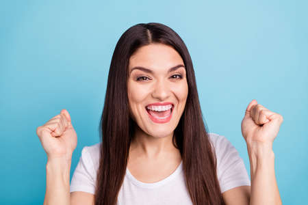 Close up photo of excited rejoicing overjoyed woman showing you her fists toothily smiling enjoying her victory while isolated with blue background