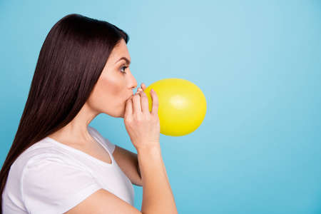 Close up photo of charming nice cute serious focused woman inflating her air ball while isolated with blue background