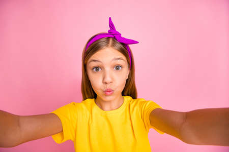 Self-portrait of her she nice attractive lovely cheerful cheery pre-teen girl wearing yellow t-shirt fooling having fun free time sending you kiss isolated over pink pastel background