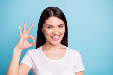 Close up photo of toothy smiling cute pretty sweet woman showing you ok sign of victory while isolated with blue background Stockfoto