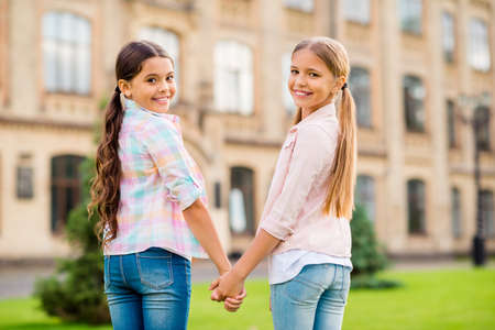 Profile side view portrait of two nice attractive lovely charming cheerful cheery friendly pre-teen girls holding hands spending day weekend rest relax free time