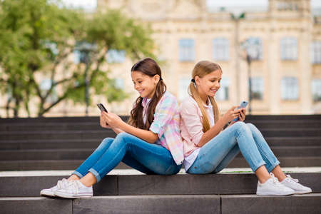 Profile side view of two nice attractive lovely cheerful cheery focused pre-teen girls chatting online internet browsing app 5g spending day weekend rest relax free time outdoors