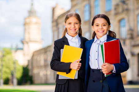 Portrait of pretty kids with pigtails ponytails holding note books wearing black blazers skirt outside