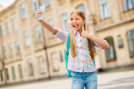 Portrait of humorous funny kid with pigtails ponytails grimace make photo approve courses hold rucksack backpack wear plaid t-shirt denim jeans stand outside Stock fotó - 129152302