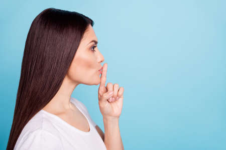Close up copyspace photo of charming cute woman showing point finger on her lips for all to keep silent while isolated with blue background