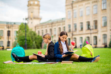Full length photo of cute girls with brunette blonde pigtails ponytails sit on grass outdoors in campus wear black blazers socks have rucksack backpack
