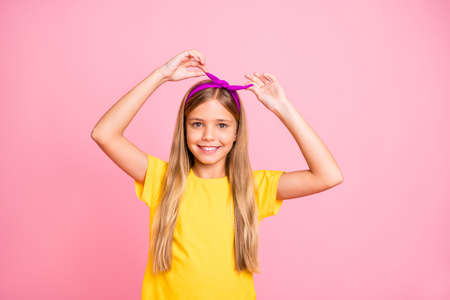 Close-up portrait of her she nice-looking attractive lovely winsome cheerful cheery pre-teen girl wearing yellow t-shirt fastening head band isolated over pink pastel background