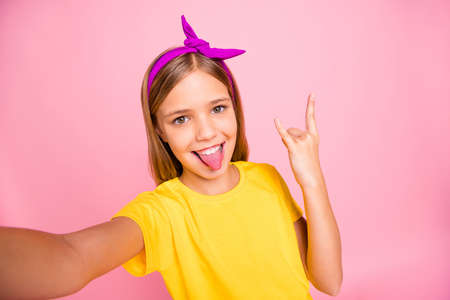 Self-portrait of her she nice attractive lovely crazy cheerful cheery pre-teen girl wearing yellow t-shirt showing horn symbol heavy metal rock roll having fun isolated over pink pastel background