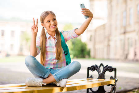 Full body photo of cheerful student having pigtails ponytails make photo v-sign hold backpack rucksack wear plaid t-shirt denim jeans sit with folded legs