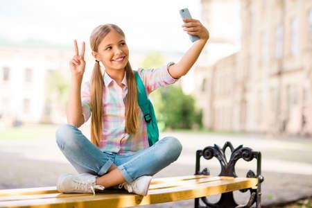 Ganzkörperfoto eines fröhlichen Studenten mit Zöpfen Pferdeschwänze machen Foto V-Schild halten Rucksack Rucksack tragen kariertes T-Shirt Denim Jeans sitzen mit gefalteten Beinen