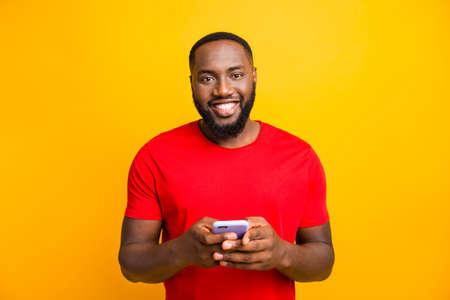 Photo de simple bon mignon bel homme noir tenant son téléphone avec les deux mains souriant à la caméra tout en isolé avec un fond jaune