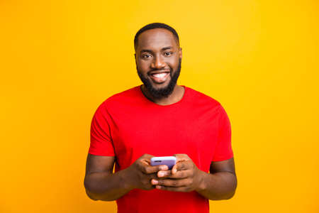Photo of simple good cute handsome black man holding his phone with both hands smiling at camera while isolated with yellow background Foto de archivo