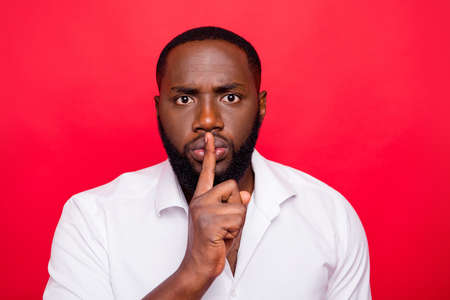 Dark skin guy begging to stop talking and keep silence wear white shirt isolated red background