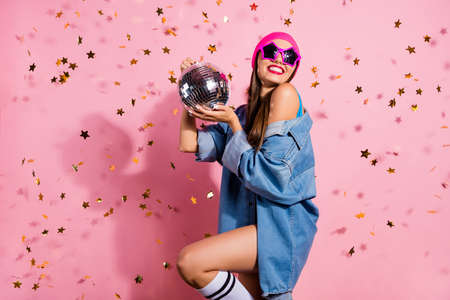 Portrait of elegant party youth holding mirror ball wearing denim jeans jacket eyewear eyeglasses isolated over pink background