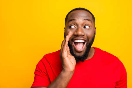 Close up photo of cheerful positive playful man telling someone secrets of him announcing important information while isolated with yellow background Foto de archivo - 129185718
