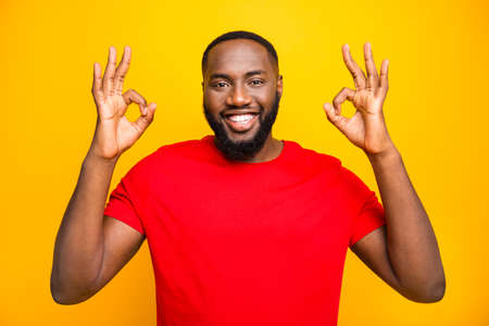 Photo of cheerful rejoicing man having nice deal for you showing you double ok sign friendly smiling while isolated with yellow background