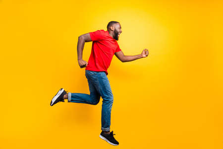 Full length body size photo of casual running man wearing jeans denim who aspires to achieve what he has planned while isolated with yellow background