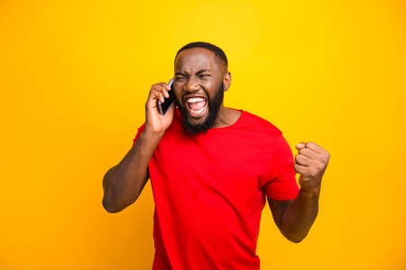 Photo of overjoyed black man knowing that he became winner of something so rejoicing enjoying news information while isolated with yellow background