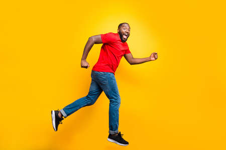 Full length body size photo of casual running man who aspires to achieve what he has planned while isolated with yellow background
