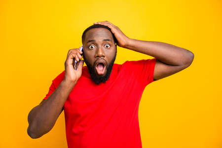Photo of feared trembling black man with his hand holding head hearing some bad news while talking by phone while isolated with yellow background