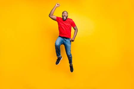 Photo pleine longueur de la taille du corps d'un homme sautant portant un t-shirt rouge en jean se réjouissant de sa victoire à quelque chose tout en étant isolé sur fond jaune