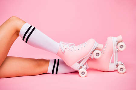 Cropped photo of girls foot wearing four -wheeled equipment quads lying isolated over pink background Stock Photo
