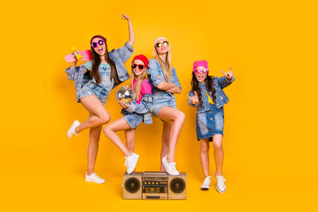 Full length size photo of group of four people carefree students having fun discotheque white parents are absent. Wearing denim outfit showing horned signs isolated yellow background