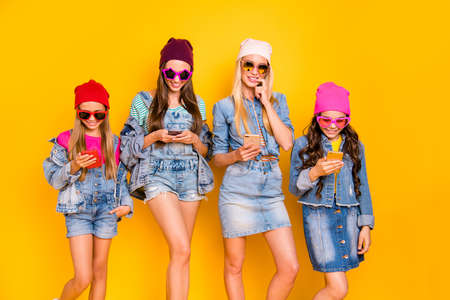 Photo of four cheerful positive flirty mother and daughter mom blonde brunette and teen babies using digital gadget devices receiving likes and comments isolated bright background
