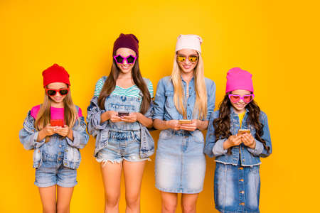 Close-up photo of group of four people influencers using posting following subscribing new sites searching news reading news-feed wearing hat cap sunglass isolated bright background