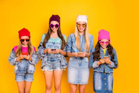 Foto ravvicinata di un gruppo di quattro persone influencer che utilizzano la pubblicazione dopo l'iscrizione a nuovi siti alla ricerca di notizie che leggono feed di notizie indossando cappello berretto occhiali da sole isolato sfondo luminoso