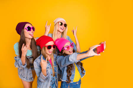 Close-up photo of cool carefree charming nice ladies showing tongue-out heavy metal symbols small photographer taking self picture of fellow friendship group people isolated yellow background Фото со стока