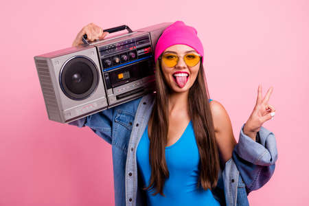 Close-up portrait of nice attractive glamorous cheerful cheery positive comic childish playful straight-haired girl carrying boombox showing v-sign isolated over pink pastel background Stockfoto