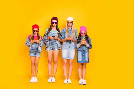 Full body photo of four confident concentrated people youngsters teenagers holding using telephones in hands texting receiving sending digital e-mails isolated bright background Stockfoto