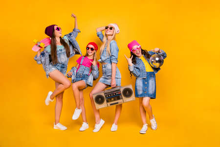 Full body photo of crazy carefree wearing street style denim outfit showing horned signs having fun entertainment using cassette player four little dancers clubbing isolated yellow background