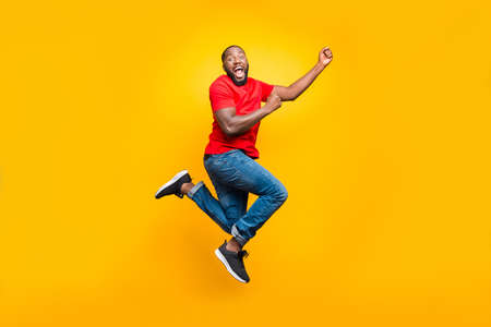 Full length body size photo of black man wearing red t-shirt having caught something invisible and now dragging it while isolated with yellow vivid background Standard-Bild