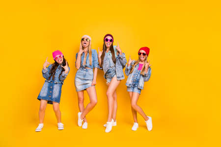 Full length body photo of group of four carefree careless best girlfriends feeling good style having perfect colorful caps wearing denim skirts showing heavy metal symbol isolated yellow background