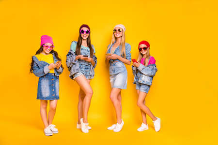 Full length photo of four nice positive cool millennials using modern technology following stars users on social network browsing reading news isolated yellow background Stockfoto