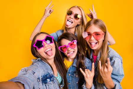 Best friendship concept. Close-up photo of group of four people having cool vacation spending free summer time together showing heavy metal symbol isolated yellow background