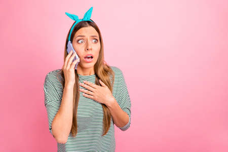 Pretty lady speaking over telephone not believe bad happening wear striped pullover isolated pink background Reklamní fotografie