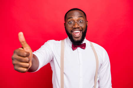 Dark skin manager guy raising thumb up recommending good product wear specs white shirt isolated red background