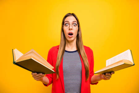 Portrait of impressed school girl with eyeglasses eyewear holding books dictionaries screaming unbelievable isolated over yellow background Stockfoto