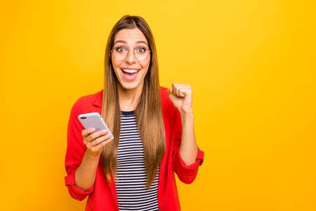 Portrait of impressed lady with eyeglasses eyewear holding device raising fists screaming yeah wow omg isolated over yellow background Stock Photo