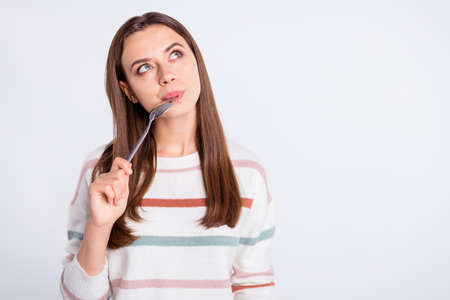 Very hungry lady holding spoon into mouth dream of tasty meal wear striped pullover isolated white background Фото со стока - 129214660