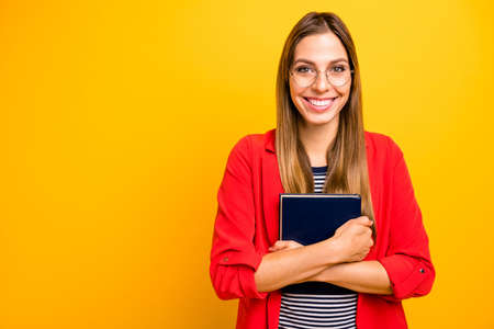 Portrait of content college hipster with eyeglasses eyewear hugging book isolated over yellow background