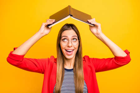 Portrait of cute lady holding encyclopedia over her head screaming wow omg wearing eyeglasses eyewear isolated on yellow background